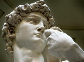 Close-up detail shows Michelangelo's statue of David at the Accademia museum in Florence
